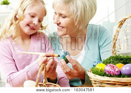 Little girl helping her grandma with painting eggs for Easter