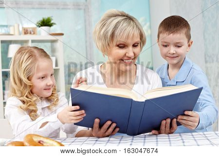 Granny reading a fairy tale to little kids