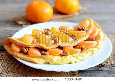 Delicious omelette with fruit and nuts on plate and on wooden table. Fried omelette stuffed with fresh mandarines and walnuts. Healthy vegetarian food. Breakfast eggs recipe. Vintage style. Closeup
