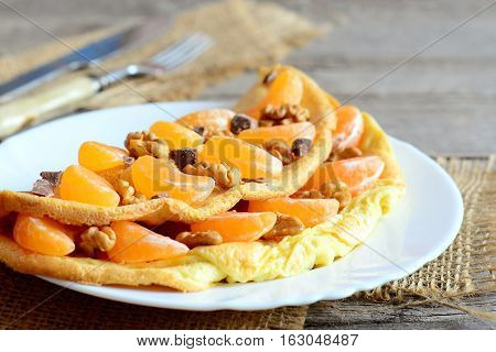 Delicious omelette with fruit, nuts and chocolate on the plate. Fried omelette stuffed with fresh mandarines, walnuts and chocolate. Sweet tasty dessert. Breakfast eggs recipe. Vintage style. Closeup