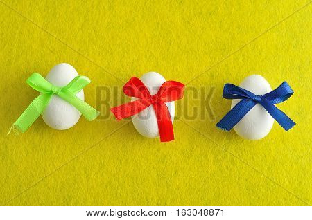 Three white easter eggs with different color bows isolated on a yellow background