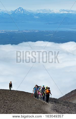 AVACHA VOLCANO KAMCHATKA PENINSULA RUSSIA - AUGUST 7 2014: Hiking on Kamchatka - group of tourists and travelers climbing to top of Avachinsky Volcano on background of Avacha Bay and volcano.