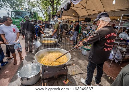Bangkok Thailand - November 01 2016 : Thai people crowd dressed in black take free food and drink in funeral of His Majesty King Bhumibol at royal field near the Grand Palace in Bangkok.