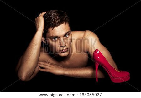 beautiful tanned male model posing near red female shoes boat