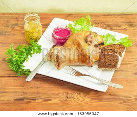 Baked ham hock with bunch of parsley and lettuce and bread on a square white dish beet horseradish sauce and French mustard knife and fork on a surface of old wooden planks