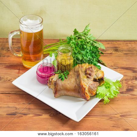Baked ham hock with lettuce and parsley beet horseradish sauce French mustard on a square white dish glass of lager beer on an old wooden surface