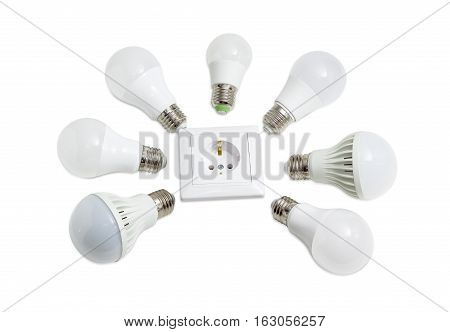 Several different domestic light emitting diode lamp with a sized E27 male screw base around the power socket on a light background