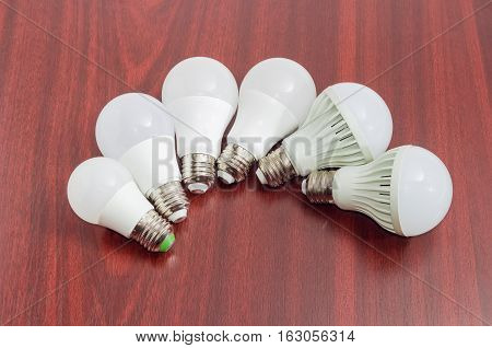 Several different domestic light emitting diode lamps with a sized E27 male screw base on a dark wooden surface