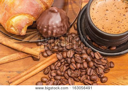Fragment of black ceramic cup with freshly brewed coffee latte closeup on the background of roasted coffee beans cinnamon sticks chocolate truffle and croissant on a wooden surface