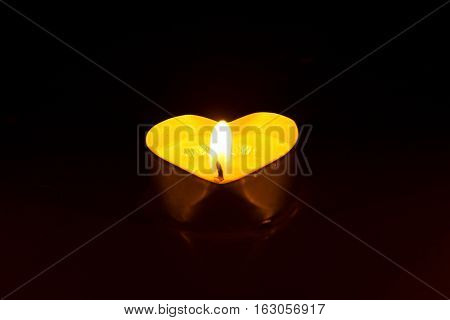 Small Round Candle With Heart-shaped Tablet Is Lit In The Dark