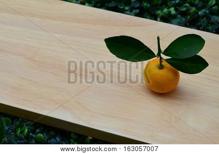 Fresh organic orange with leaves on wooden board - healty lifestyle