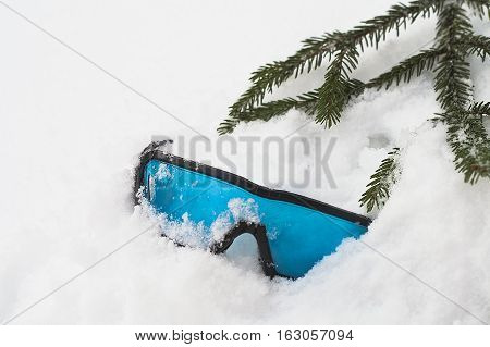 Abandoned ski glasses seems broken laid in the snow next to a fir tree branch concept of winter holidays