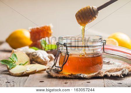 Honey in jar with honey dipper, ginger and lemon on wooden background