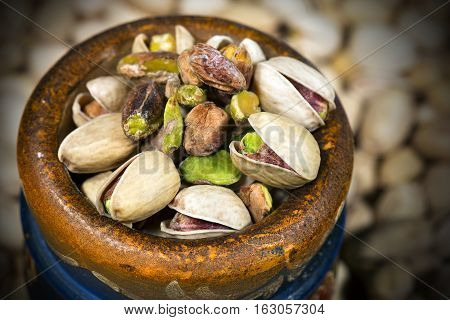 Group of roasted and salted pistachios in a wooden bowl with dark shadows - Macro photography