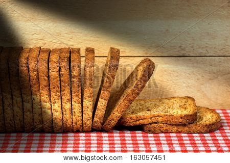 Row of healthy rusks of wholemeal flour on a table with red and white checkered tablecloth and wooden wall