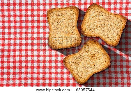 Three healthy rusks of wholemeal flour on a table with red and white checkered tablecloth