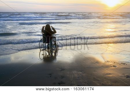 Sunset on the beach handicapped woman in wheelchair