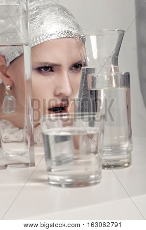 Woman Looks Through Glasses Filled With Water