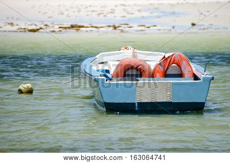 Old Boat With Two Life Buoys Moored Near The Shore.