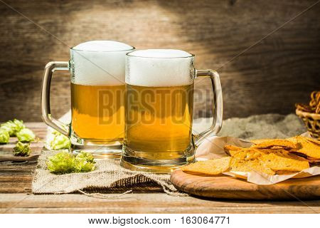 Couple beer mug with hop and chips on boards on linen cloth on wooden table