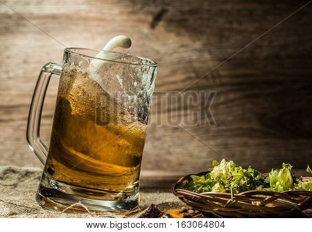 Beer spilling from cup on linen cloth beside hops in basket