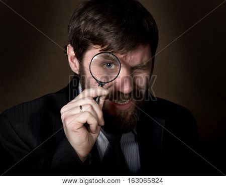 portrait of handsome young businessman looking through magnifying glass on a brown background.