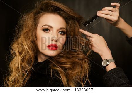 Stylist corrects hairstyle beautiful brunette in studio