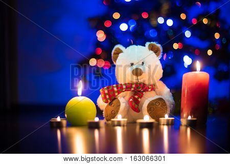 A teddybear surrounded by burning candels. Candle light. Cozy holiday eve. Romantic date.