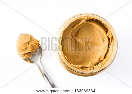 Creamy peanut butter and spoon isolated on white background