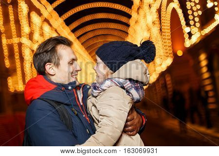 Daddy and daughter in Christmas on street on background of buildings with garlands