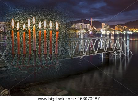 Low key composite image with menorah with glitter lights of burning candles and coastal cityscape of Eilat - famous Israeli resort. Image symbolizes Jewish holiday of Hanukkah