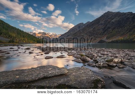 Rocky Lake Surrounded With Mountains Under Blue Sky, Altai Mountains Highland Nature Autumn Landscape Photo. Beautiful Russian Wilderness Scenery Image.