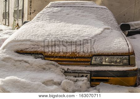 Yellow car, front view of old golden car, bright golden old car in snow, old-fashioned car, yellow oldtimer