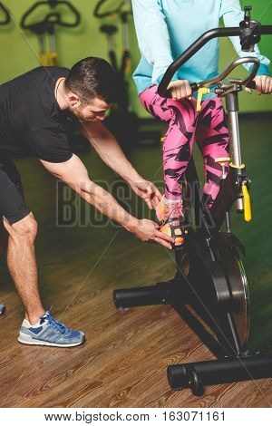 Sportwoman on exercise bike engaged with trainer