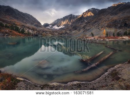Blue Muddy Water Lake Surrounded By Mountains Reflecting The Sky, Altai Mountains Highland Nature Autumn Landscape Photo. Beautiful Russian Wilderness Scenery Image.