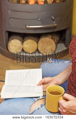 Woman is sitting down and holding yellow tea mug and open book. Burning wood stoves are in the background. Vertically. The letters in the book are intentionally blurred.