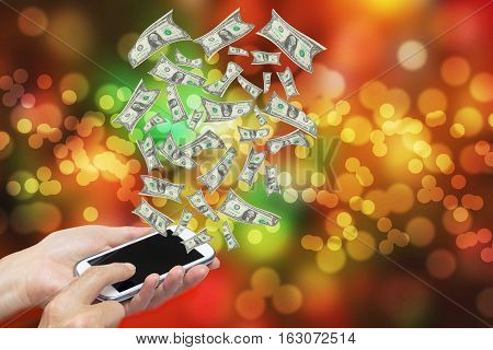 Spending money concept. Female hands are holding some smart phone. Banknotes are flying on the blurred color light background. All potential trademarks are removed.