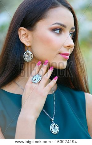 beautiful girl with a unique silver jewelry posing in a spring garden
