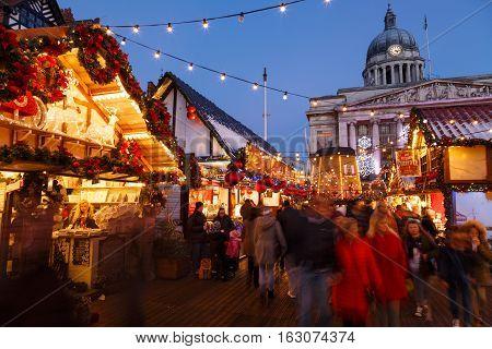 NOTTINGHAM ENGLAND - DECEMBER 22: Families enjoying Nottingham Christmas Market in the evening. In Nottingham England. On 22nd December 2016.