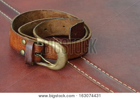 old worn leather belt with brass buckle