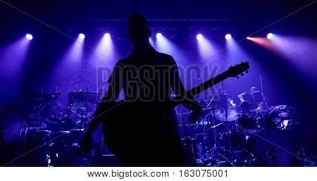 The guitarist plays solo. Close-up. Dark background. Smoke