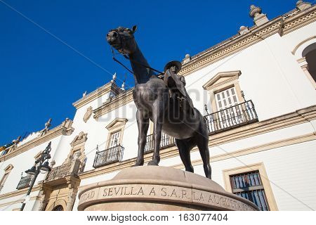 Seville Spain - November 192016: Bullfight arena.View of the facade of Real Maestranza de Caballeria and the monument to the mother of King Juan Carlos in Seville Spain