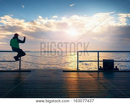 Tourist Sit On Mole Handrail And Takes Pictures. Man Enjoy Morning At Sea.