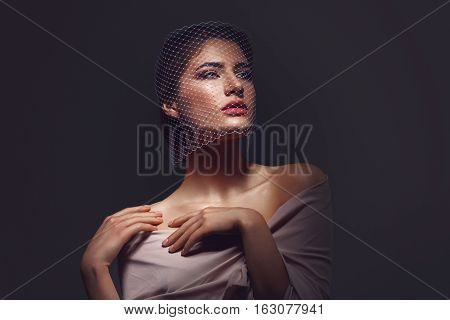 Portret of beautiful young woman with natural makeup. Face covered in veil net. Hands with beige nude manicure. Studio shot on black background. Copy space.