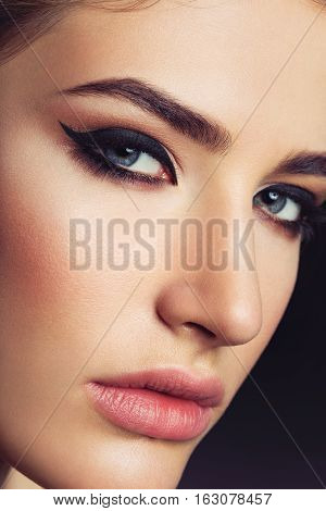 Close-up portrait of beautiful young woman with cat eye make-up. Beauty macro shot.