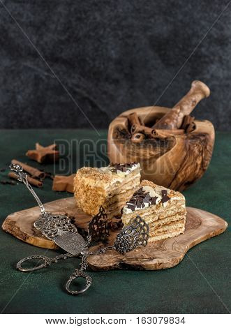 Honey cake with spices and vintage tools on dark background. Sweet food