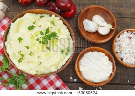 Mashed Potatoes with chopped green onion and parsley leaves. Mayonnaise, garlic, salt and chilli peppers on rustic table