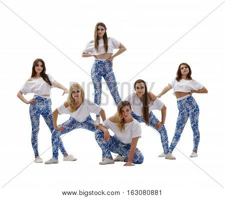 Sexy girl dance group posing in white tops and blue leggings in studio standing together in erotic pose