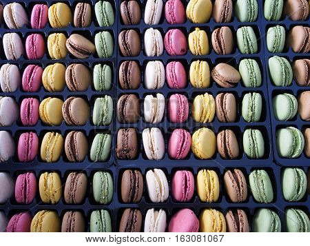 Rows and columns of multicolored macarons, traditional French cookies.