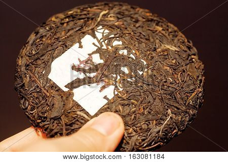 Tea Pu-erh in shape of cake traditional chinese drink. Popular antioxidant tea from China in the hand of person.